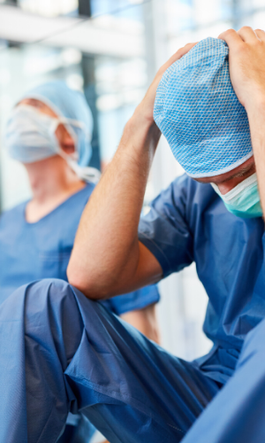 picture of a doctor in blue scrubs sitting down and holding his head