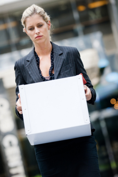 photo of a business woman carrying her office belonging in a box after being terminated