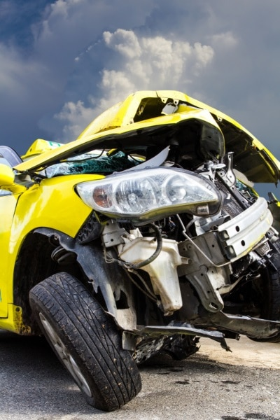picture of a yellow car involved in a motor vehicle accident